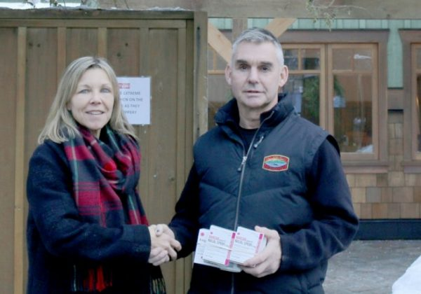 Lorinda Strang, executive director of Orchard Recovery Center hands over Naloxone kits to Bowen Island fire chief Ian Thompson