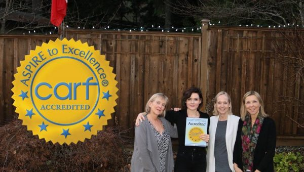 Suzan Ross, Jess Malkin, Joanna Journet and Lorinda Strang proudly displaying Orchard Recovery Center's 3 year CARF Accreditation