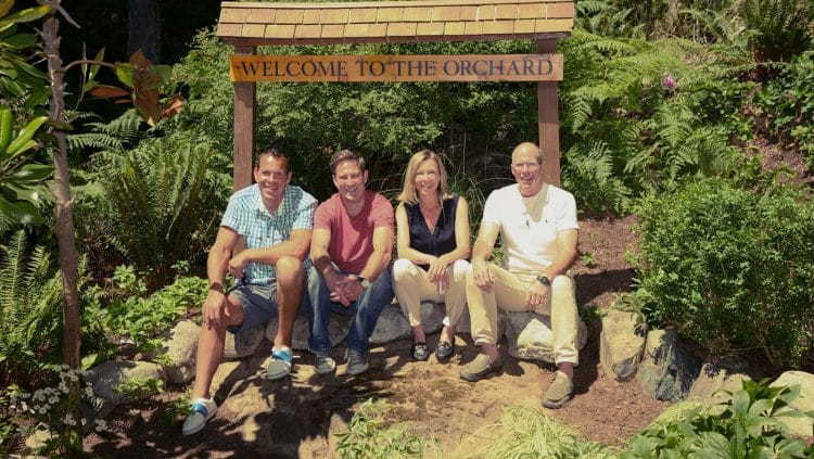 Lorinda Strang, Executive Director Orchard Recovery Center sitting with alumni under the sign at the Residence