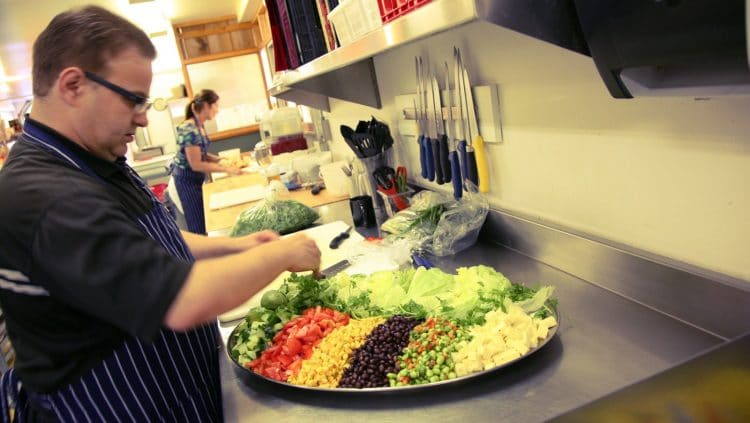 Chef Gord Hedge preparing a fresh salad in Orchard Recovery Center's main kitchen
