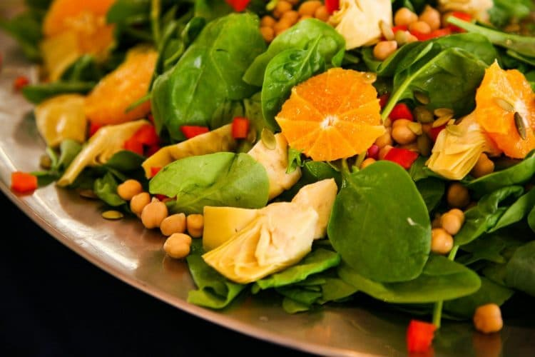 Spinach salad, topped with artichoke and orange provides a delicious meal.