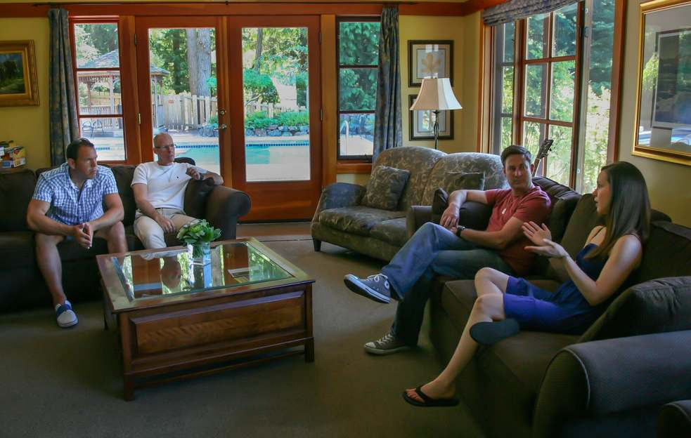Clients engaging in a discussion in the living room of Orchard Recovery Residence
