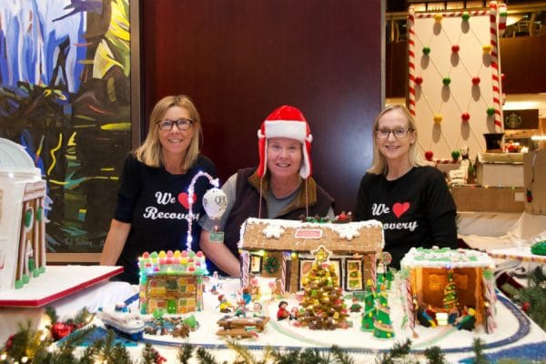 "Three women, one in a Santa hat, two wearing t-shirts saying ""We Heart Recovery"" standing behind several ginger bread houses, picnic tables, Christmas trees, people and a ferry on railroad tracks."